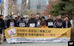 "FILE- Victims of Japan's forced labor and their family members arrive at the Supreme Court in Seoul, South Korea, Nov. 29, 2018. The sign reads "" Mitsubishi Heavy Industries apologize and compensate victims."""
