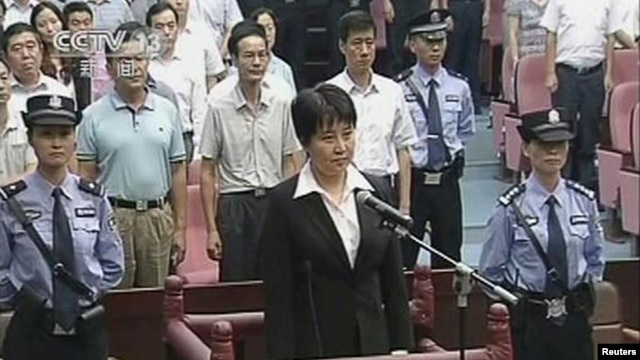 Gu Kailai (C), wife of ousted Chinese politician Bo Xilai, stands at the defendant's dock during her trial at Hefei Intermediate People's Court in this still image taken from video, August 20, 2012.