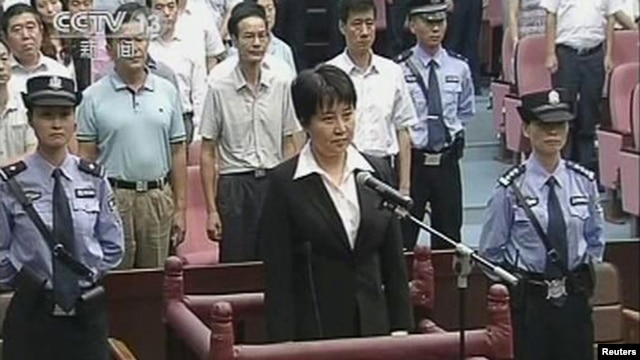 Gu Kailai (C), wife of ousted Chinese Communist Party Politburo member Bo Xilai, stands at the defendant's dock during a trial in the court room at Hefei Intermediate People's Court in this still image taken from video, August 20, 2012.