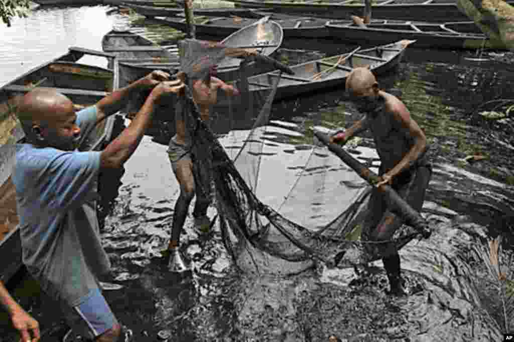 Fishermen sort out their fishing net at the bank of a polluted river in Bidere community in Ogoniland in Nigeria's delta region.