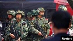 Cảnh sát đứng gác bên ngoài ga xe lửa nơi 3 người thiệt mạng và 79 người bị thương trong 1 vụ đánh bom và tấn công bằng dao tại Urumqi, Tân Cương, 1/5/2014.