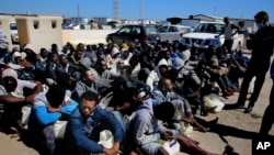 FILE - African illegal migrants wait to receive medial assistance after being rescued by coast guards, in Tripoli, Libya, April 11, 2016.