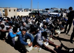 FILE - African illegal migrants wait to receive medial assistance after being rescued by coast guards, in Tripoli, Libya, April 11, 2016. More than 100 migrants were rescued by two coastal guards on Monday after their boat started sinking in the sea.