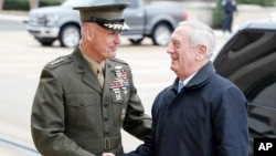FILE - Chairman of the Joint Chiefs Gen. Joseph Dunford, left, shakes hands with Secretary of Defense James Mattis as Mattis arrives at the Pentagon in Washington, Jan. 21, 2017.