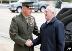 FILE - Chairman of the Joint Chiefs Gen. Joseph Dunford, left, shakes hands with Secretary of Defense James Mattis as Mattis arrives at the Pentagon, Jan. 21, 2017.