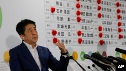 아베 신조 일본 총리가 10일 일본 도쿄 자민당사에 설치된 참의원 선거 상황실에서 개표 현황을 살피며 기자들의 질문에 답하고 있다.