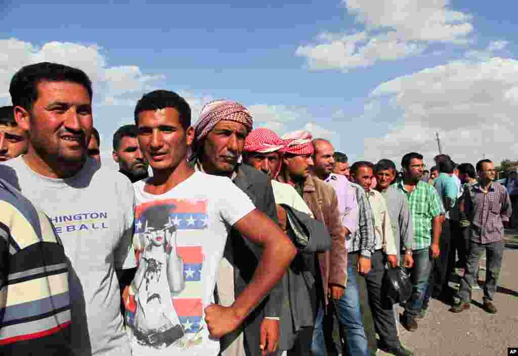 Syrian refugees return home at Mursitpinar crossing gate near Suruc, Turkey, Sept. 25, 2014.