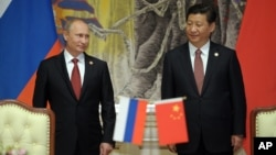 Russia's President Vladimir Putin and China's President Xi Jinping, right, smile during signing ceremony in Shanghai, China, on May 21, 2014.