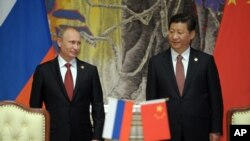 FILE - Russia's President Vladimir Putin (L), and China's President Xi Jinping smile during signing a ceremony in Shanghai, China, May 2014.
