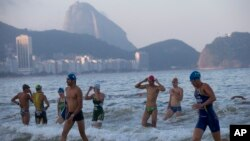 Triathletes leave the water after swimming in the Copacabana beach during training ahead of the Triathlon Olympic Qualifier event, in Rio de Janeiro, Brazil, July 31, 2015.