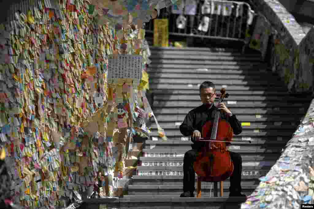 David Wong, a 41-year-old cellist, performs in front of a wall posted with messages of support for pro-democracy protesters at the Admiralty district, Hong Kong.