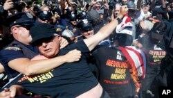 Un oficial lucha con un manifestante que quemaba una bandera, en las cercanías de la Quicken Loans Arena de Cleveland.