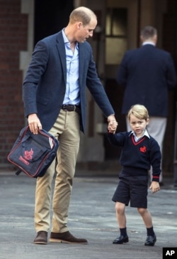 Britain's Prince William, left, accompanies Prince George as he arrives for his first day of school at Thomas's school in Battersea, London, Sept. 7, 2017.