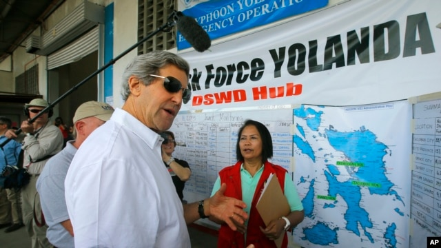 U.S. Secretary of State John Kerry visits a relief distribution center during a tour of the damage from Typhoon Haiyan in Tacloban, Philippines, Dec. 18, 2013.