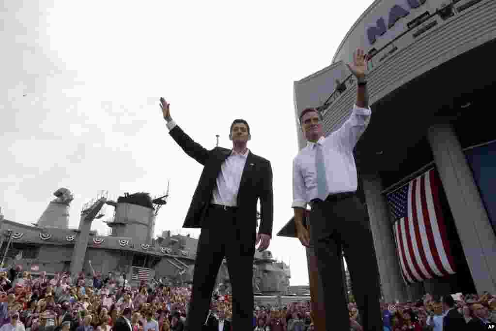 O candidato presidencial republicano e ex-governador de Massachusetts, Mitt Romney, (dir.) e o candidato a vice-presidente, congressista de Wisconsin Paul Ryan, saúdam apoiantes num comício na cidade de Norfolk.