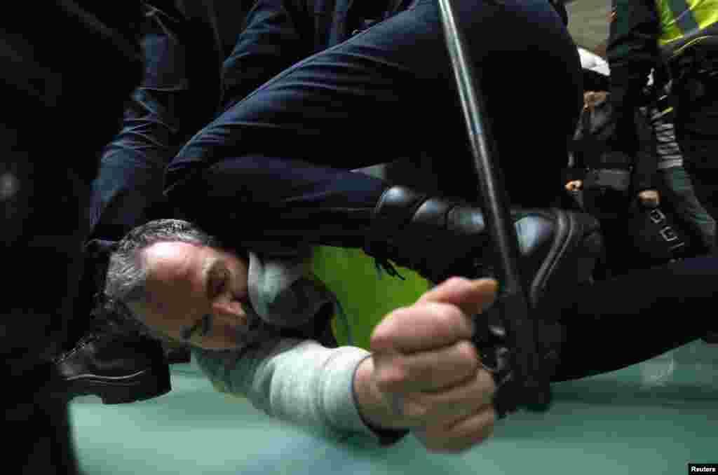 Un agent de la compagnie aérienne Iberia est maitrisé par la police anti-émeutes expagnole lors de heurts à l'aéroport Barajas de Madrid.