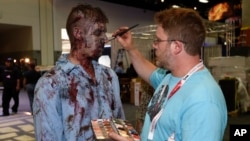 "A zombie has his makeup done at AMC's ""Walking Dead"" booth before Preview Night at Comic-Con International, held at the San Diego Convention Center, July 8, 2015."