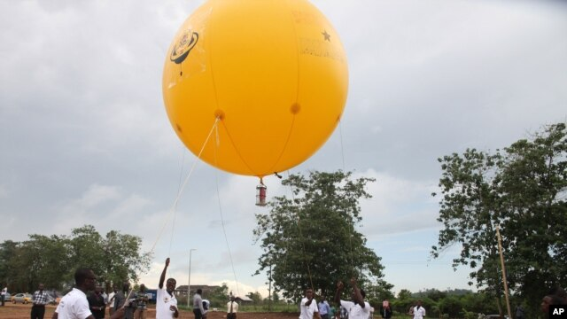 Students use a balloon to launch Deployable CanSat, a soda-can sized model of a satellite, All Nations University, Koforidua, Ghana, May 15, 2013.
