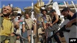 Các binh sĩ của phe nổi dậy đạp lên một bức tượng của ông Gadhafi bên trong dinh thự Bab Al-Aziziya tại Tripoli, Libya