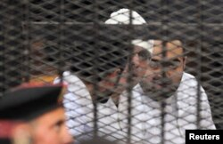 Political activists Ahmed Maher, Ahmed Douma (L) and Mohamed Adel (R) of the April 6 movement look on from behind bars in Abdeen court in Cairo, Egypt, Dec. 22, 2013.