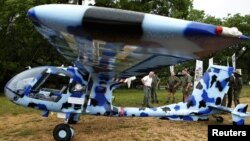 Rangers look at an anti-poaching aircraft named Seeker, which is being shown to reporters at the Kruger National Park in South Africa, December 4, 2012.