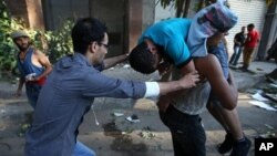 22일 이집트 수도 카이로에서 무르시 찬반 시위대가 충돌한 가운데, 반대 시위대들이 부상당한 동료를 옮기고 있다.