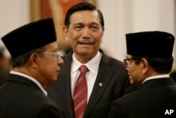 Indonesia's Security Chief Luhut Panjaitan, center, talks with Cabinet Secretary Pramono Anung, right, and Coordinating Minister for the Economy Darmin Nasution, before the inauguration ceremony at Presidential Palace in Jakarta, Wednesday, Aug. 12, 2015.
