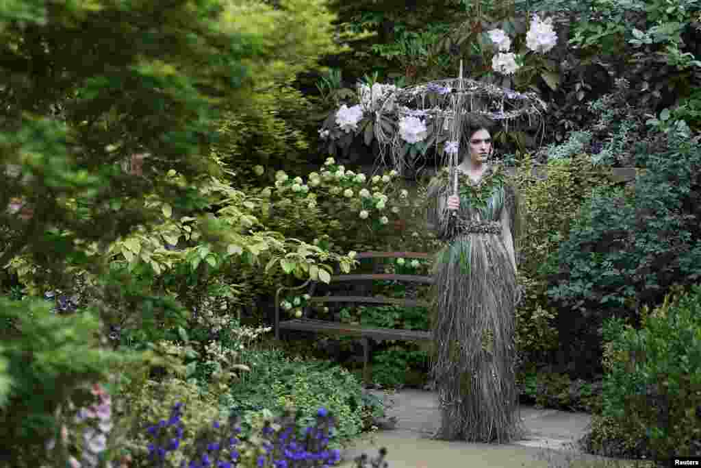 A women wearing a dress of fresh flowers designed by Zita Elze poses for photographers in the M & A Centenary Garden during media day at the Chelsea Flower Show in London.