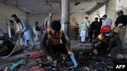 Petugas keamanan memeriksa lokasi ledakan di sebuah madrasah di Peshawar pada 27 Oktober 2020. (Foto: AFP)