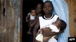 Hai anh em bế em 2 đứa em trai đứng bên ngoài một nơi tạm trú trong thủ đô Port au Prince của Haiti