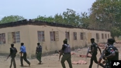 FILE - Security guards walk past a burned-out government secondary school in Chibok, Nigeria. April 21, 2014.