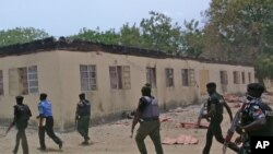 FILE - Security guards walk past a burned-out government secondary school in Chibok, Nigeria, in April 2014.