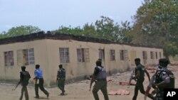 Des forces de sécurité à pied devant une école secondaire publique incendiée dans Chibok, Nigeria. 21 avril, 2014 (ARCHIVES).