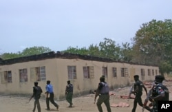 FILE - Security personnel walk past a burnt-out government secondary school in Chibok, where gunmen abducted more than 200 students, Chibok, Nigeria, April, 21, 2014.