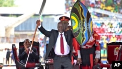 Tanzania's new President John Pombe Magufuli holds up a ceremonial spear and shield to signify the beginning of his presidency during his inauguration ceremony at Uhuru Stadium in Dar es Salaam, Nov. 5, 2015.
