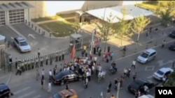 美國駐華大使駱家輝座車9月18日在北京美國駐華大使館前被抗議示威著圍堵(VOA衛視截圖 )