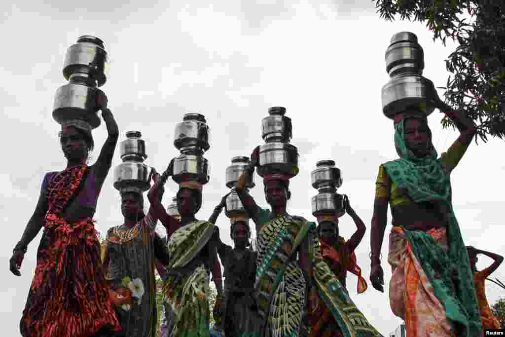 Women carry pitchers filled with water from an opening made to filter water in Thane, India.