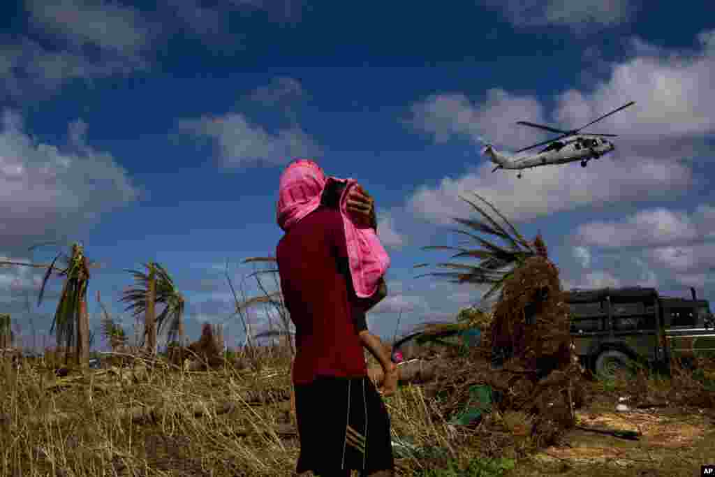 A Typhoon Haiyan survivor carries a child wrapped in a towel as he watches a helicopter landing to bring aid to the destroyed town of Guiuan, Samar Island, Philippines.