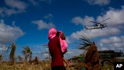 FILE - A Typhoon Haiyan survivor carries a child wrapped in a towel as he watches a helicopter landing to bring aid to the destroyed town of Guiuan, Samar Island, Philippines.