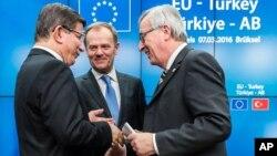 PM Turki Ahmet Davutoglu (kiri) berbicara dengan Presiden Komisi Eropa Jean-Claude Juncker (kanan) dan Presiden Dewan Eropa Donald Tusk (tengah) setelah konferensi pers di Brussels, Belgia (8/3). UNHCR hari Selasa (8/3) mengecam beberapa bagian dari kesepakatan Uni Eropa-Turki di Brussels tersebut.