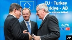 Turkish Prime Minister Ahmet Davutoglu, left, speaks with European Commission President Jean-Claude Juncker, right, and European Council President Donald Tusk, center, after a media conference at an EU summit in Brussels, Belgium, March 8, 2016.
