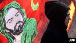 Một người Hồi giáo Shia Iraq đi ngang qua hình ảnh của Thánh Hussein.