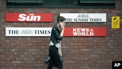 A woman speaks on her mobile phone outside the News International headquarters building that houses the top-selling newspaper The News of the World, which is closing, in east London, July 6, 2011