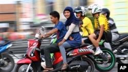 Perempuan Aceh membonceng sepeda motor di Lhokseumawe (7/1). (AP/Rahmat Yahya)
