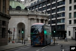A bus drives through the City of London financial district in London, Jan. 5, 2021, on the first morning of England entering a third national lockdown since the coronavirus outbreak began.
