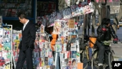 Chinese man stops at a news stand on a street in Beijing (file photo)
