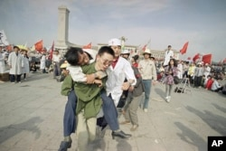 In this May 16, 1989 file photo, medics rush a Beijing university student from Tiananmen Square after he collapsed on the third day of a hunger strike in Beijing.