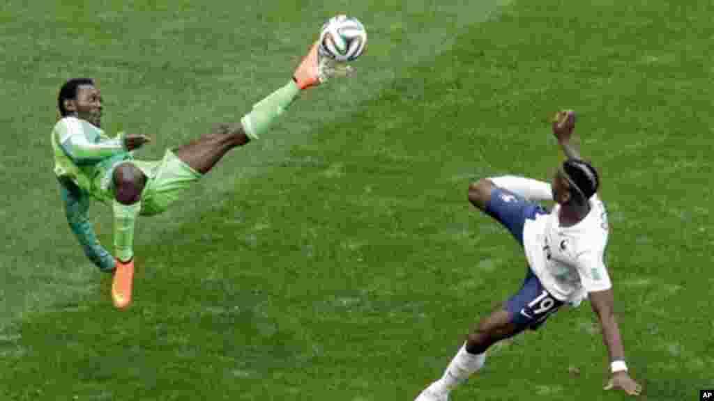 Nigeria's Juwon Oshaniwa and France's Paul Pogba challenge for the ball.