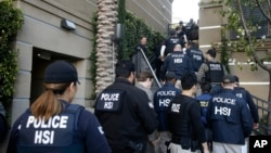 FILE - Federal agents enter an upscale apartment complex where authorities say a birth tourism business charged pregnant women between $40,000 and $100,000 for lodging, food and transportation, in Irvine, Calif., March 3, 2015.