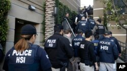 FILE - Federal agents enter an apartment complex where authorities say a birth tourism business charged pregnant women between $40,000 and $100,000 for lodging, food and transportation, in Irvine, Calif., March 3, 2015.